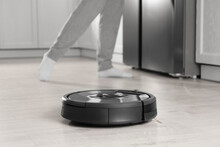 Modern Robotic Vacuum Cleaner And Blurred Woman On Background