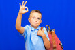 canvas print picture - Funny serious little blonde kid schoolboy red striped backpack posing isolated on blue background.showing OK gesture