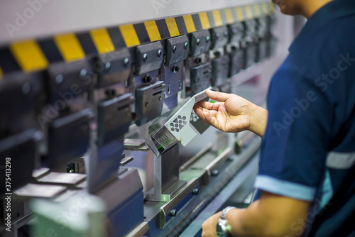 The operation of hydraulic bending machine with technician Fototapet