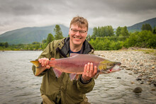 A Happy Fisherman Proudly Holding Up A Sockeye Salmon