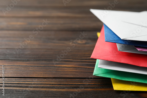 Colorful paper envelopes on wooden background, closeup Canvas Print