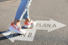 Choosing Between Plan A And Plan B. Woman Near Arrows On Road, Closeup View