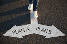 Choosing Between Plan A And Plan B. Man Near Pointers On Road, Closeup View