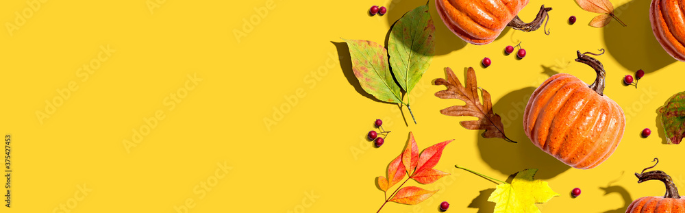 Fototapeta Autumn pumpkins with colorful leaves overhead view - flat lay