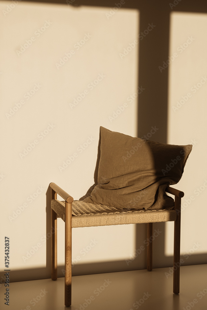 Pillow on wicker bench in sunlight shadows on the wall. Minimal interior design concept