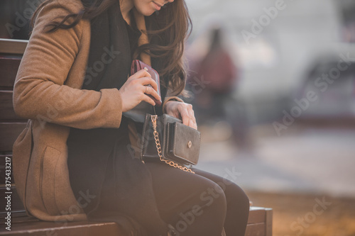 Fotografiet woman looking different stuff in her purse sitting on city bench