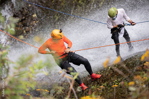 Two Amateur Man rappelling down a waterfall
