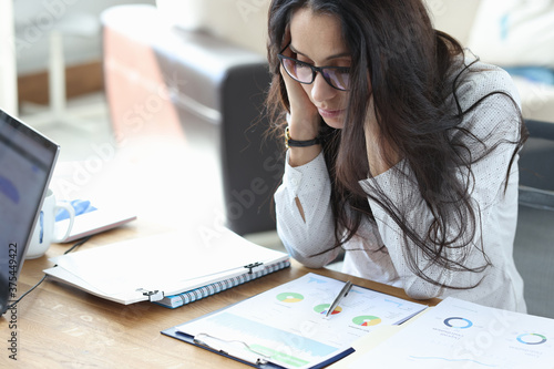 Leinwand Poster Sad woman sits at her work desk in office over charts with business indicators and holds her head