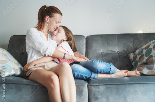 Fototapeta Young beautiful mother and her daughter child 8 years old are sitting on a gray sofa and tenderly hugging, happiness and love in the family