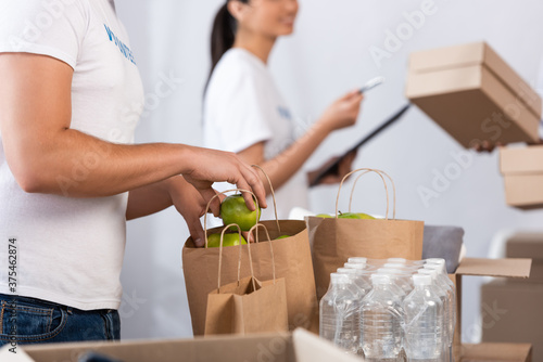 Cropped view of volunteer putting apples in paper bags near bottles of water in charity center