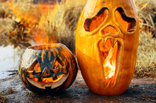 Halloween Horror Concept. Two Halloween Pumpkins Are Burning On The Shore Of The Pond, Outdoors.