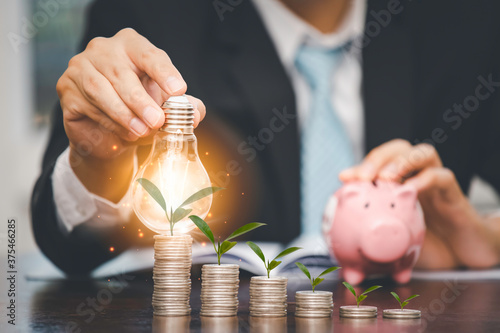 Carta da parati Businessman hand holding light bulb with line connect and Coins stack on the woo