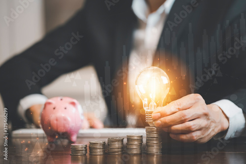 Fotografia Businessman hand holding light bulb with line connect and Coins stack on the woo