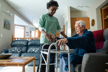 Home Caregiver Helping Senior Man With Walker In Living Room