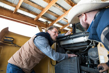 Smiling Male Ranchers Fixing T...