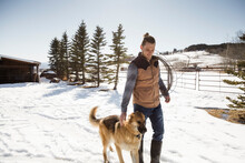 Male Rancher And Dog Walking In Snow