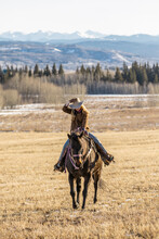 Woman Riding Horse On Ranch