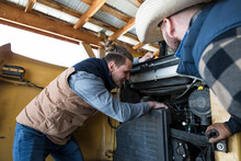 Male Ranchers Fixing Tractor E...