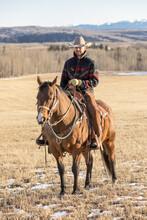 Male Rancher Horseback Riding On Sunny Ranch