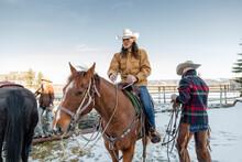 Male Rancher Horseback Riding On Snowy Ranch
