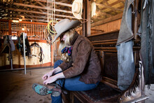 Female Rancher Putting On Cowboy Boots In Stable