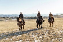 Ranchers Horseback Riding On Sunny Winter Ranch