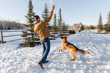 Male Rancher Playing With Dog On Snowy Winter Ranch