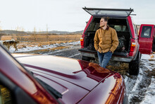 Thoughtful Male Rancher Standing Outside Truck On Snowy Road