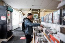 Male Customer Shopping For Records In Shop