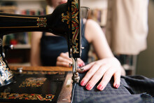 Woman Stitching Clothe On Vintage Sewing Machine