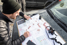 Men Looking At Map On Hood Of ...