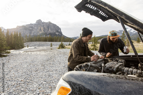 Brothers checking engine of overland SUV near mountain stream