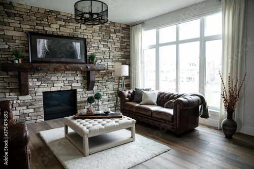 Living room with leather sofas, exposed brickwall and wooden flooring - 375479693