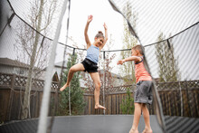 Girl And Boy Playing On Trampoline