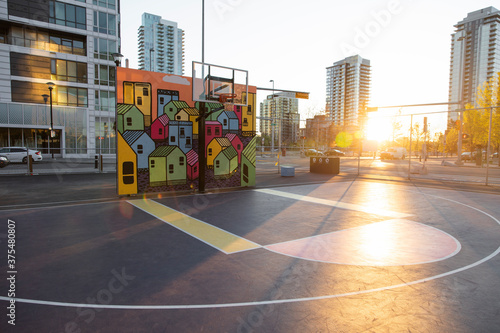 Painted mural wall behind basketball hoop on sunny urban court - 375480807