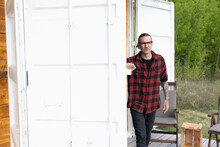 Mature Man Opening Door On Container Home