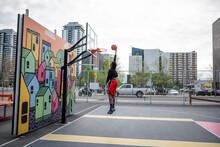 Young Man Playing Basketball O...