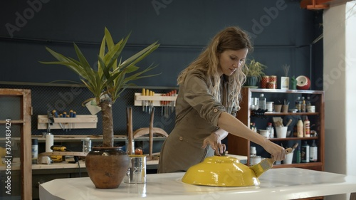 Photo A female restorer painting a yellow detail in workshop, female hands renew old furniture holding a paintbrush