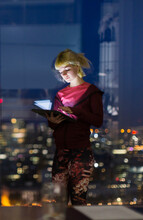 Young Businesswoman With Digital Tablet Working Late At Office Window