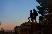 Silhouette Young Hiker Couple Enjoying View Of Moon From Rock At Dusk