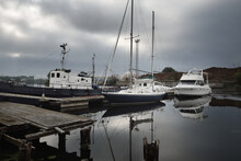 Old Tugboat, Elegant And Modern Sailboats Moored To A Pier In A Yacht Marina, Close-up. Storm Sky. Symmetry Reflections On The Water. Port Of Riga, Latvia. Transportation, Sailing, Fishing, Recreation