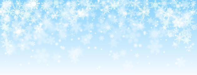 Christmas background of falling snowflakes in light blue colors