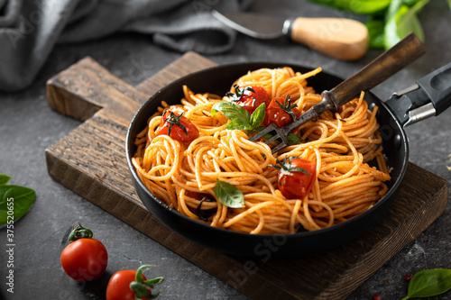 Obraz na plátně pasta in a black pan on a dark background , italian cuisine, selective focus