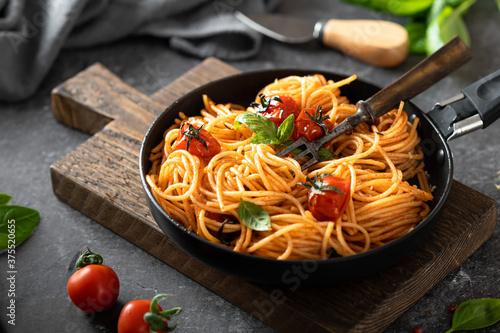 Fotografiet pasta in a black pan on a dark background , italian cuisine, selective focus
