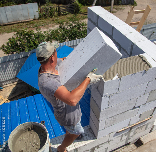 Photo A worker builds the walls of a house from aerated concrete bricks