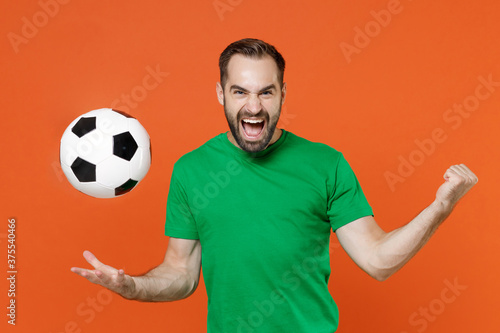 Foto Screaming man football fan in green t-shirt cheer up support favorite team throwing soccer ball clenching fist isolated on orange background studio portrait