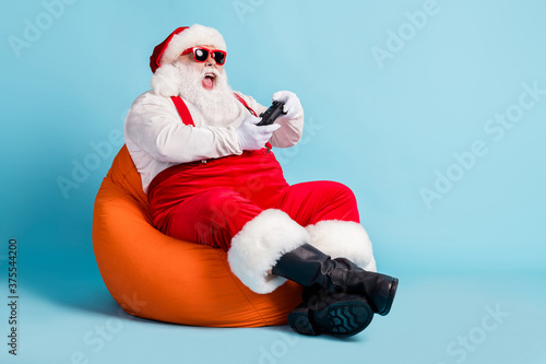 Full length photo of retired old man beard hold gamepad lose game playstation sit orange beanbag wear red santa x-mas costume suspender boots sunglass cap isolated blue color background