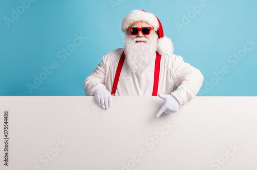 Photo of pensioner grandfather grey beard direct fingers empty space demonstrate curious proposition wear santa costume suspenders sunglass white headwear isolated blue color background