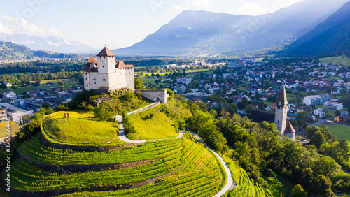 View from drone of stone Gutenberg Castle on top of green hill on background with small town of Balzers, Liechtenstein