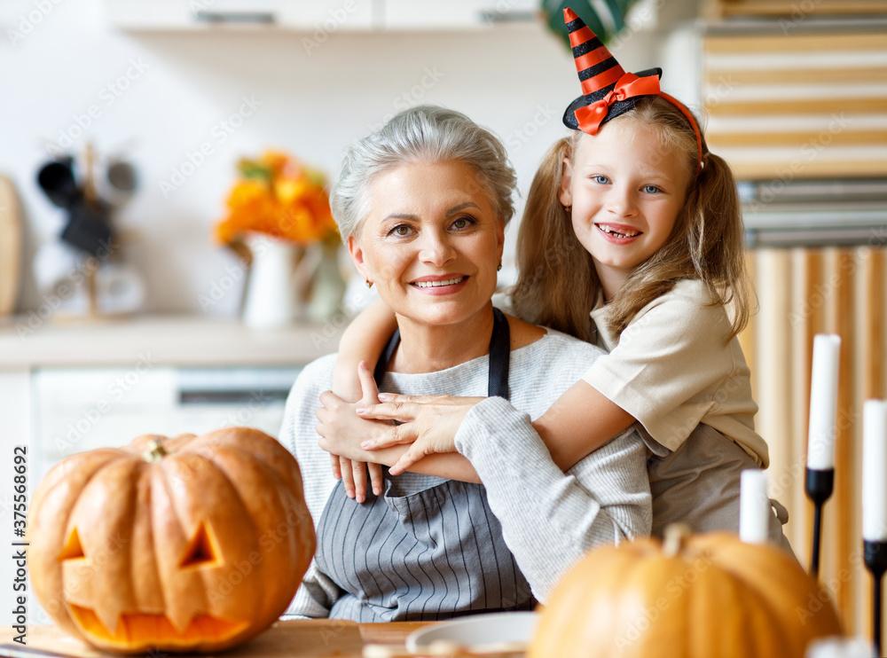 Fototapeta Happy granddaughter and grandmother preparing for Halloween celebration